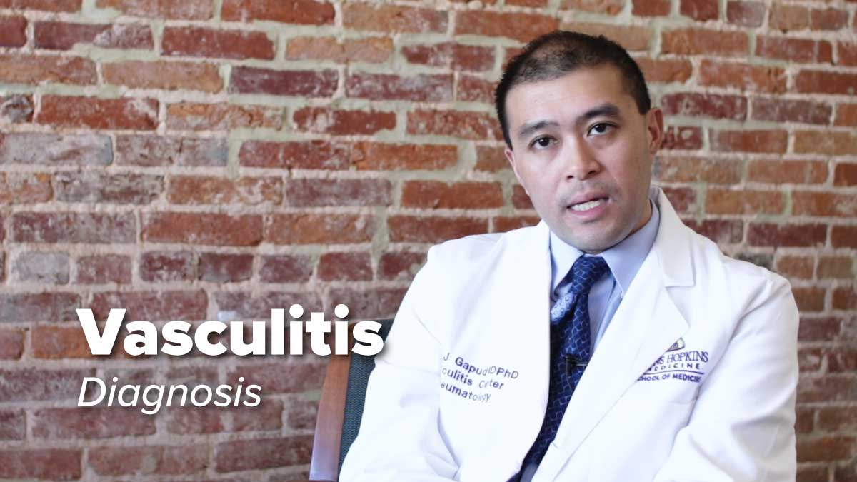 Dr. Eric Gapud sitting in a chair in front of a brick wall discussing the diagnosis of Vasculitis