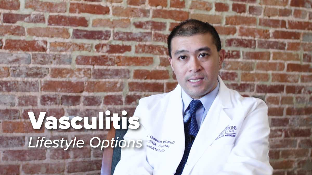 Dr Eric Gapud sitting in front of a brick wall discussing living with Vasculitis