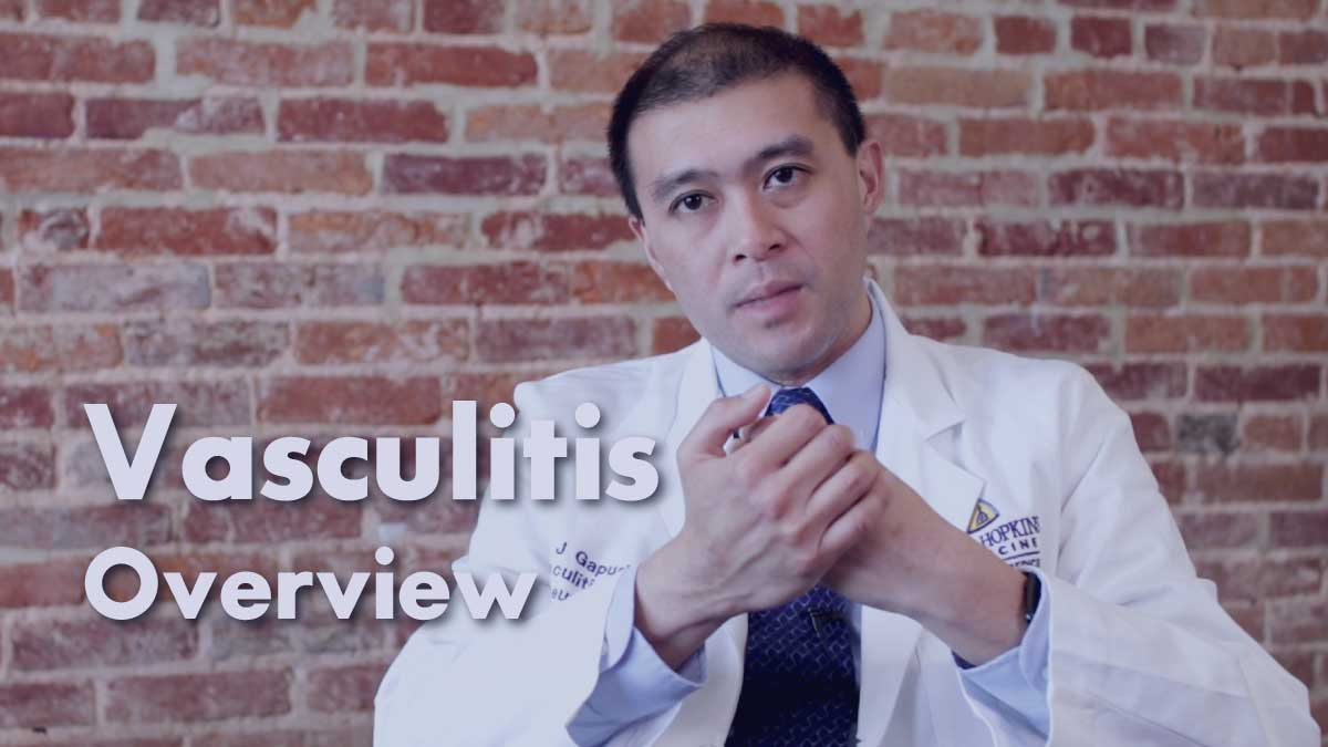 Dr. Eric Gapud sitting in a chair in front of a brick wall discussing Vasculitis